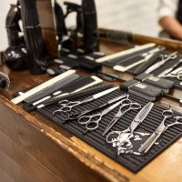 barber tools on wooden shelf and mirror in barbershop.